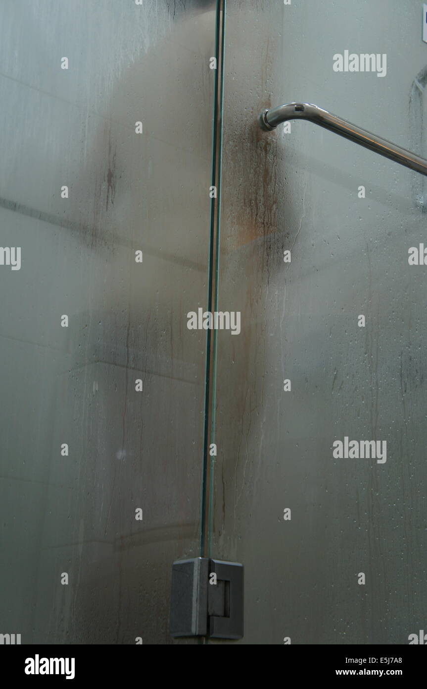 man taking shower in a shower cubicle - Stock Image