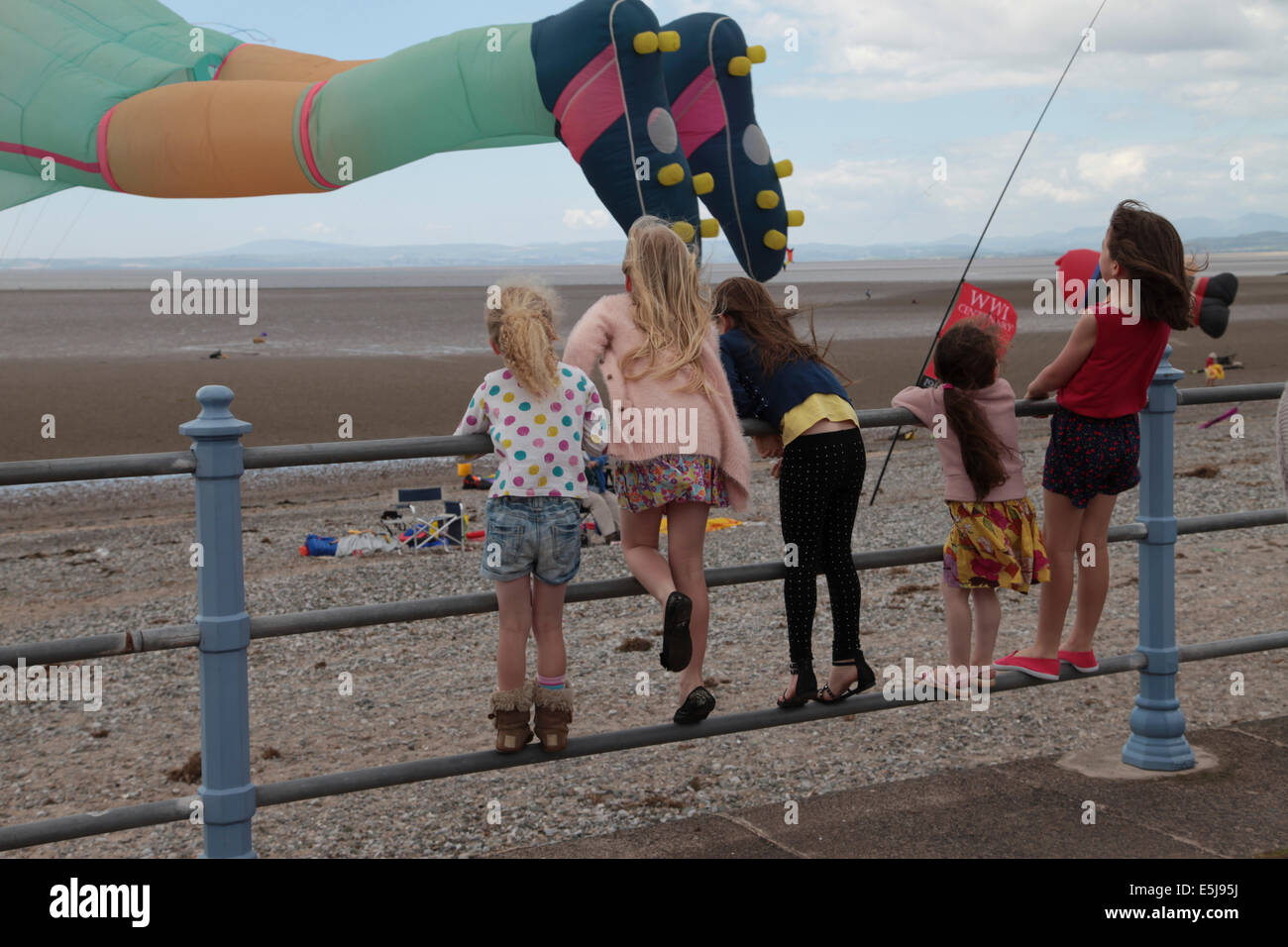 Young girls standing on railings watching a footballer kite on the beach at Morecambe Kite Festival 2014 - Stock Image