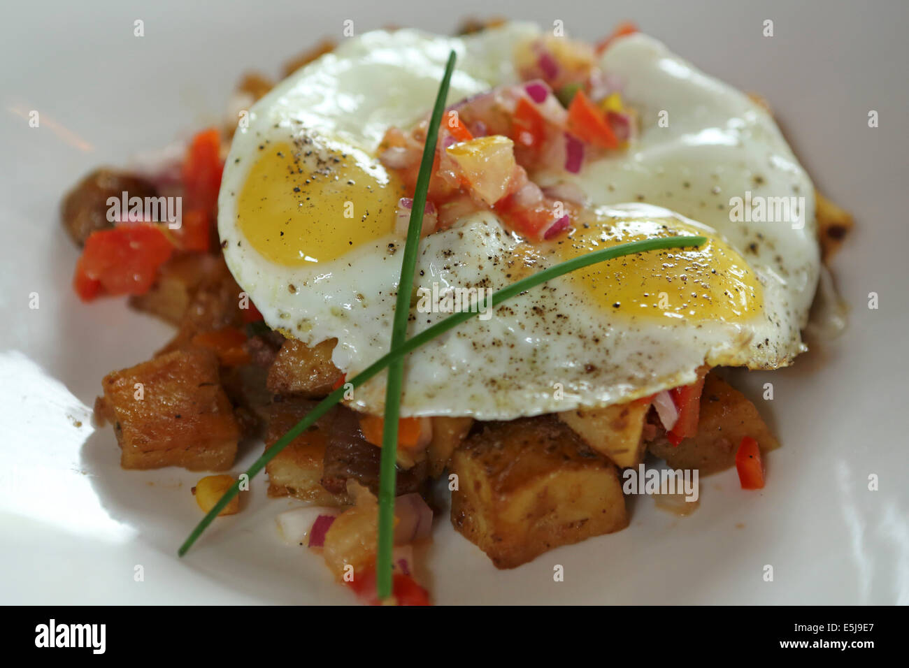 A spicy potato hash topped with two fried eggs. The dish is a popular comfort food. - Stock Image