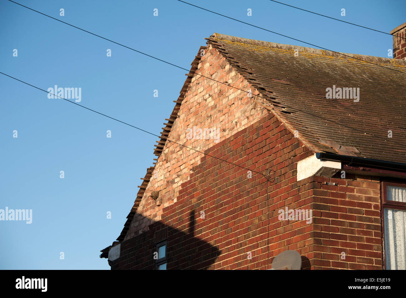 House Gable End bricks blown off storm windy ties - Stock Image