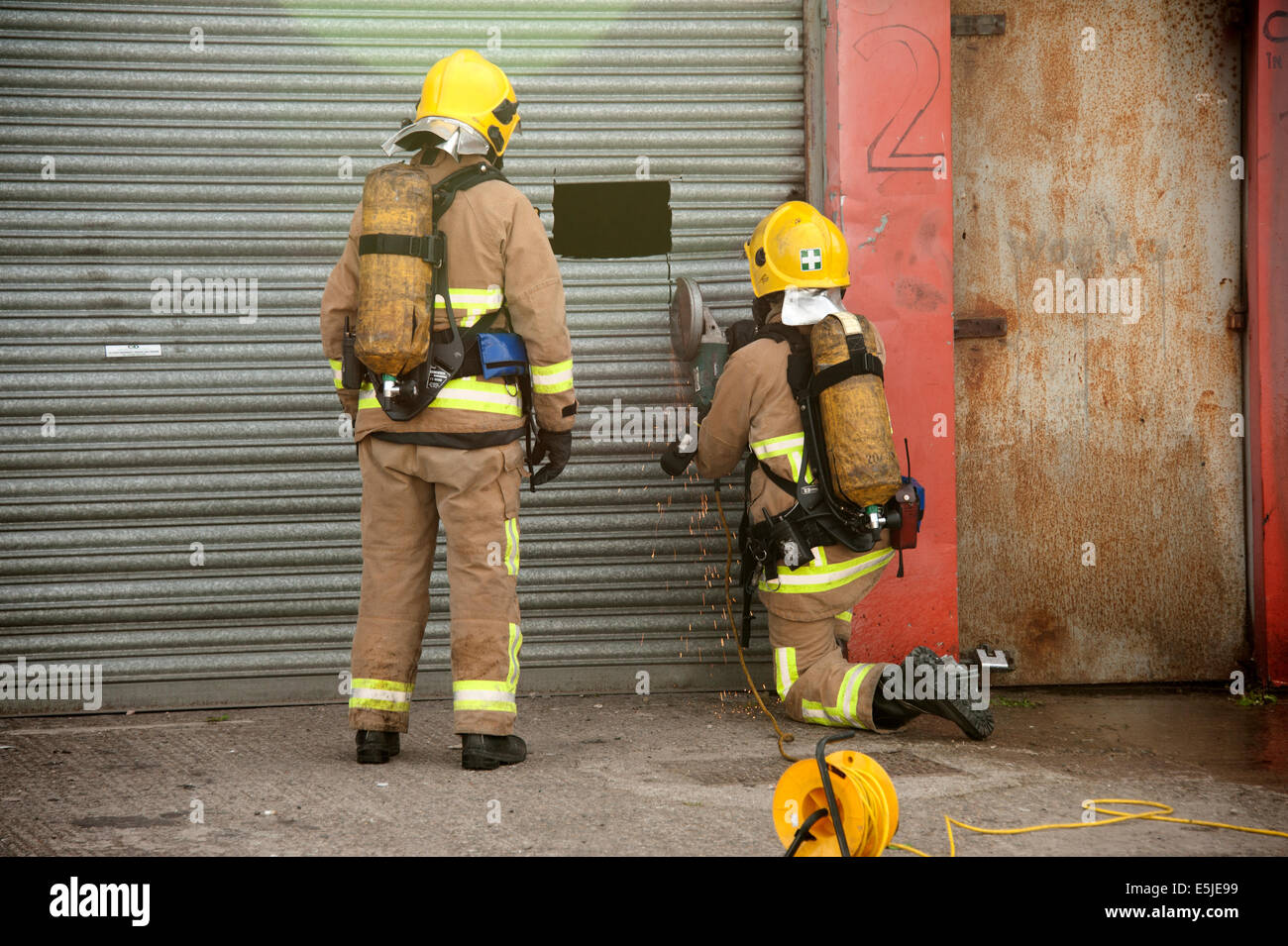 Firefighters Cutting Roller Shutter Angle Grinder Gain Access - Stock Image