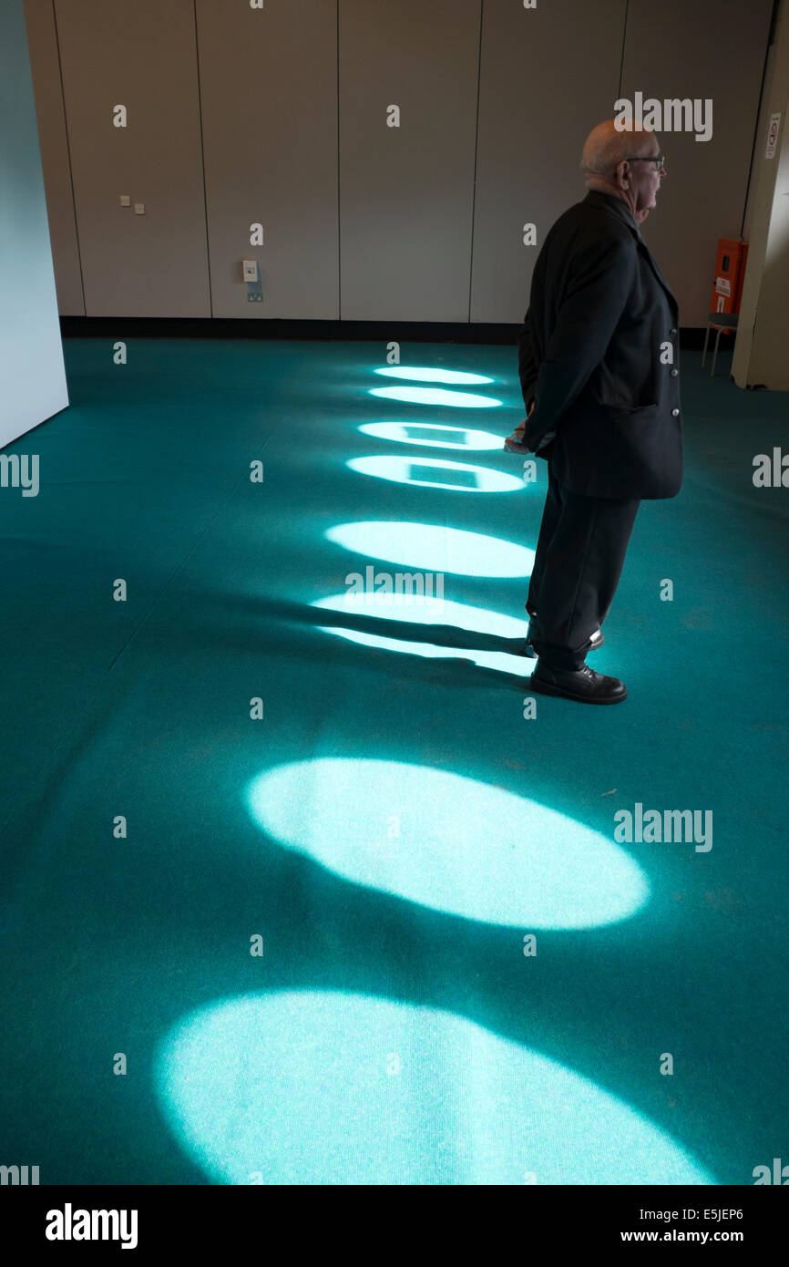 Man Standing in Pool of Sunlight Streaming Through Windows - Stock Image