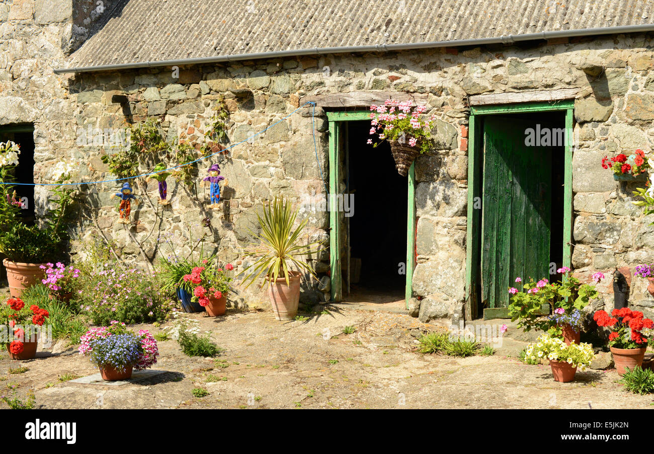 Stone cottage with potted plants outside - Stock Image