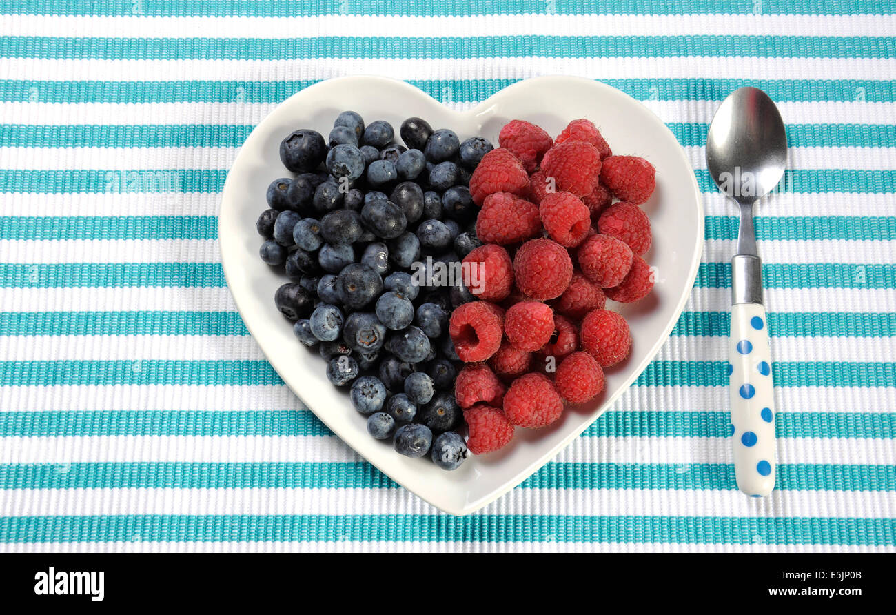 Healthy diet high dietary fiber breakfast with blueberries and raspberries in heart shape white plate on aqua blue - Stock Image