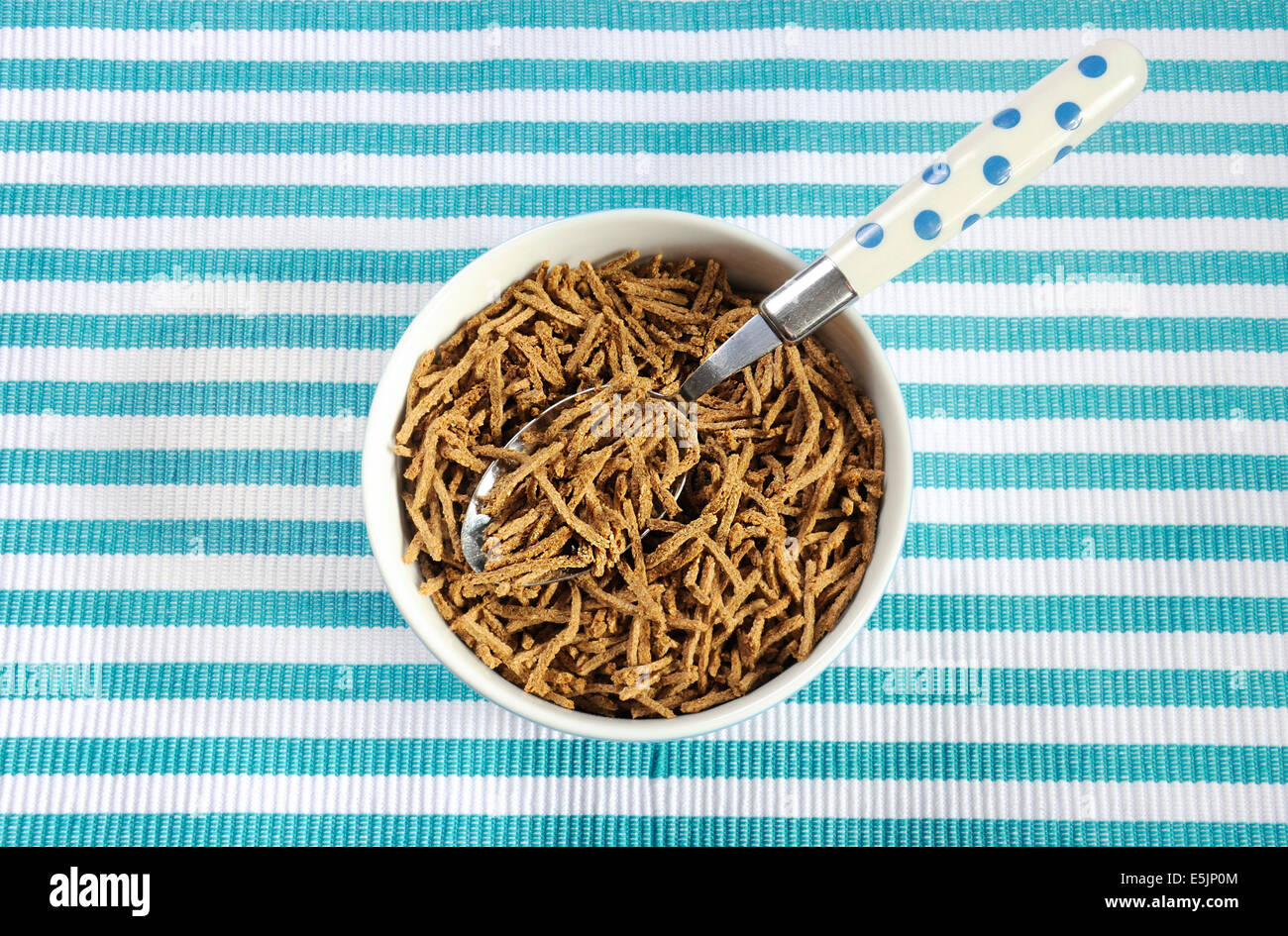 Healthy diet high dietary fiber breakfast with bowl of bran cereal on aqua blue and white place mat. - Stock Image