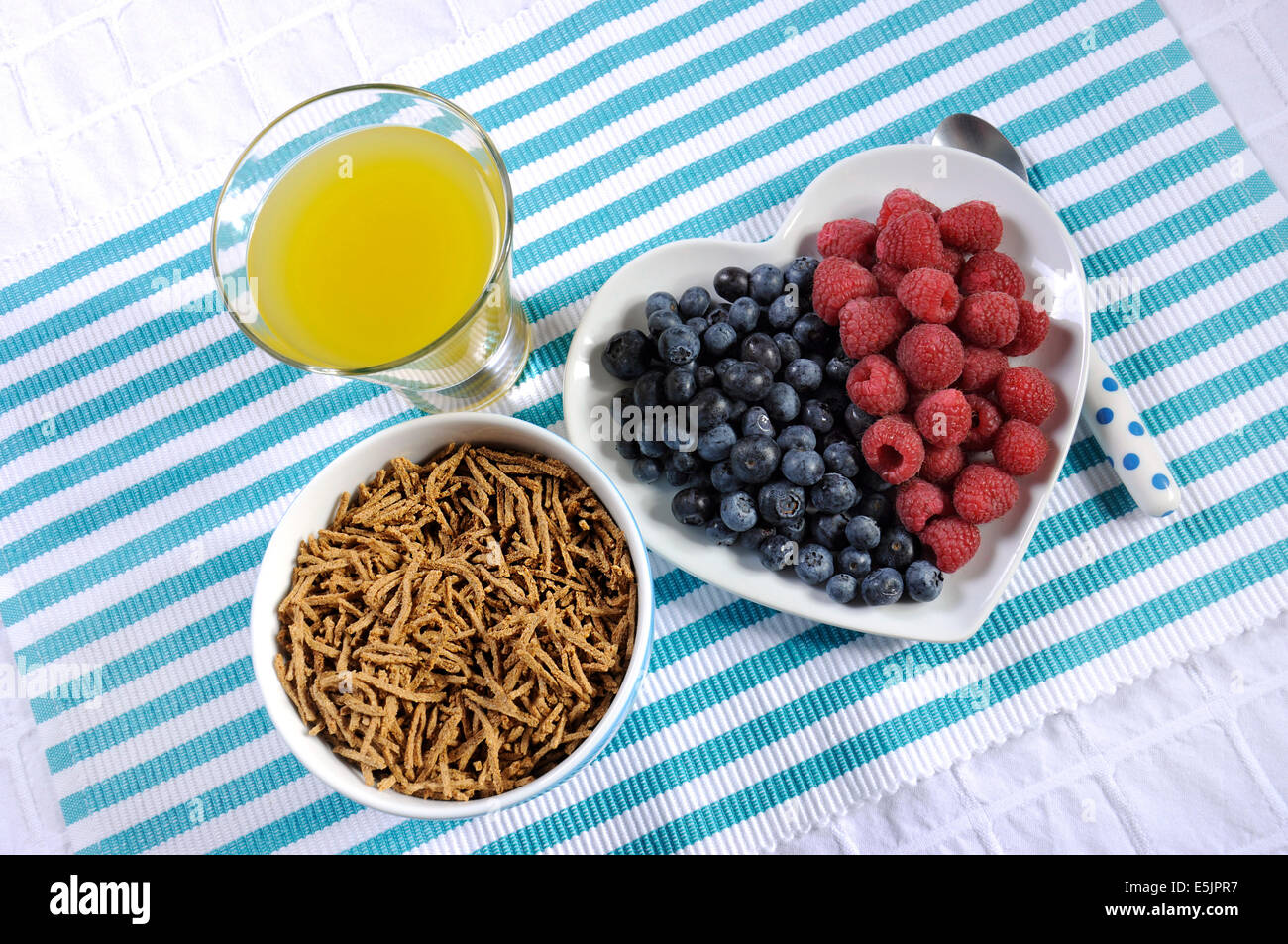 Healthy diet high dietary fiber breakfast with bowl of bran cereal and berries on white heart plate on aqua blue - Stock Image