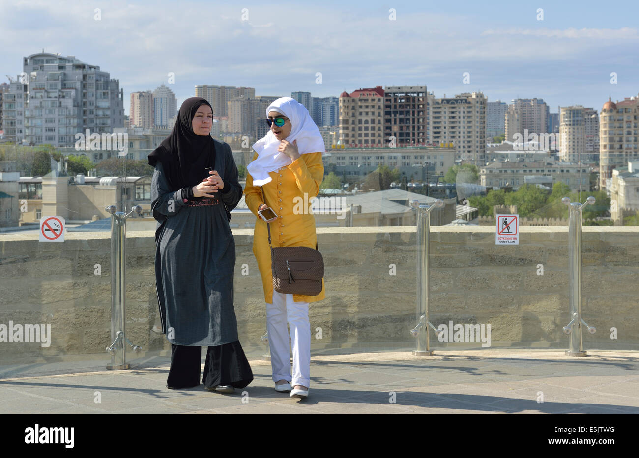 Two women on viewing platform of the Maiden Tower, Old City, Baku, Azerbaijan - Stock Image
