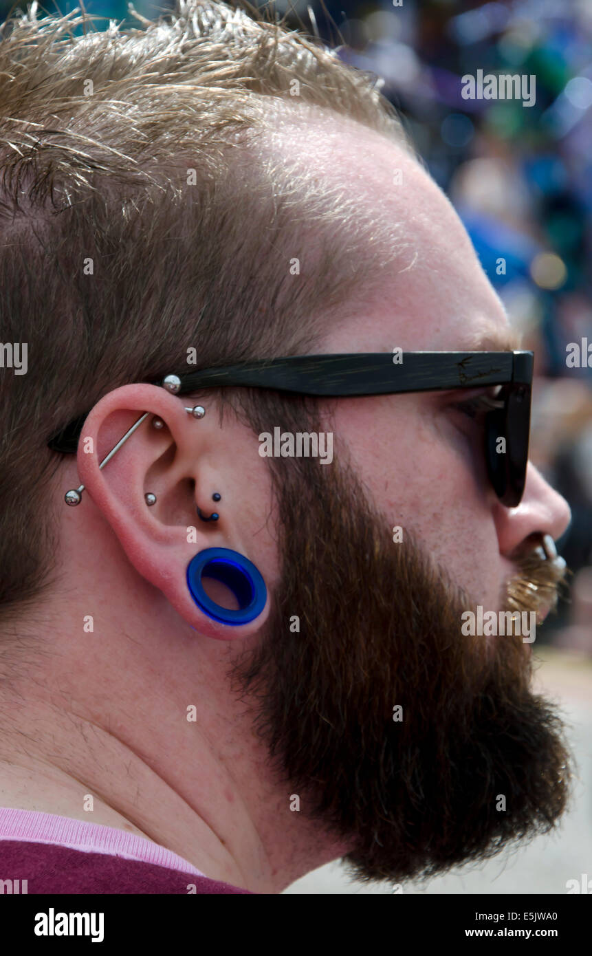 Bearded Man With Numerous Ear Piercings Watching The Carnival Part