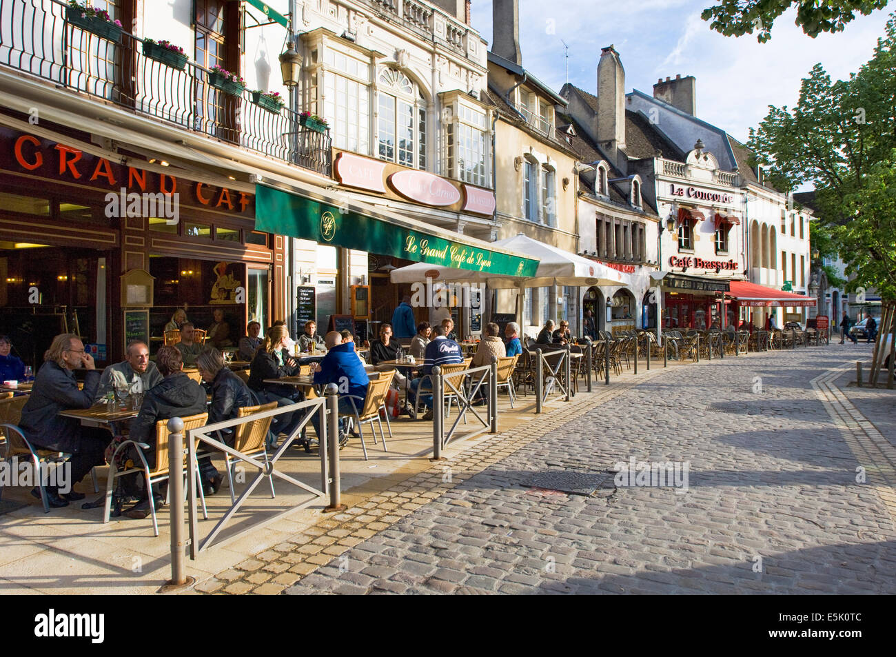 Late afternoon street café scene in Beaune, Burgundy, with typical European building and cafés lining - Stock Image