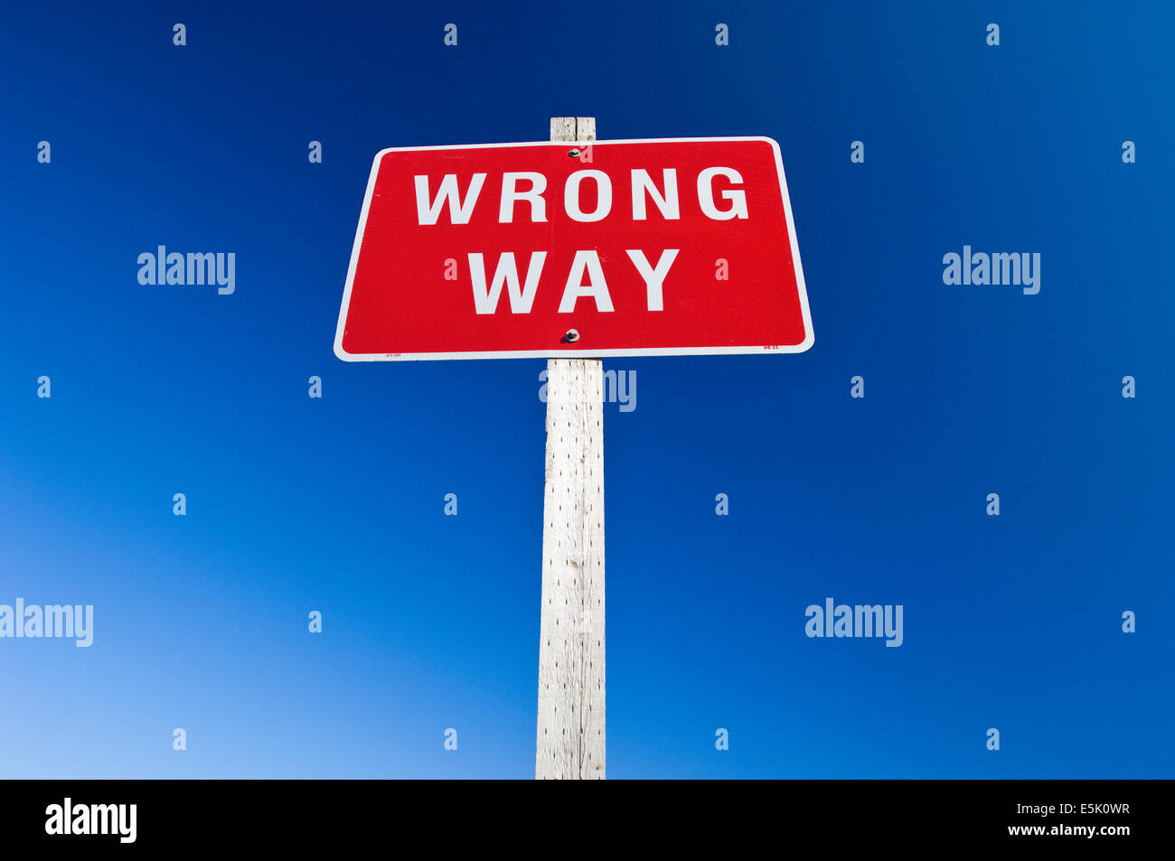 A red Wrong Way road sign against a clear blue - Stock Image