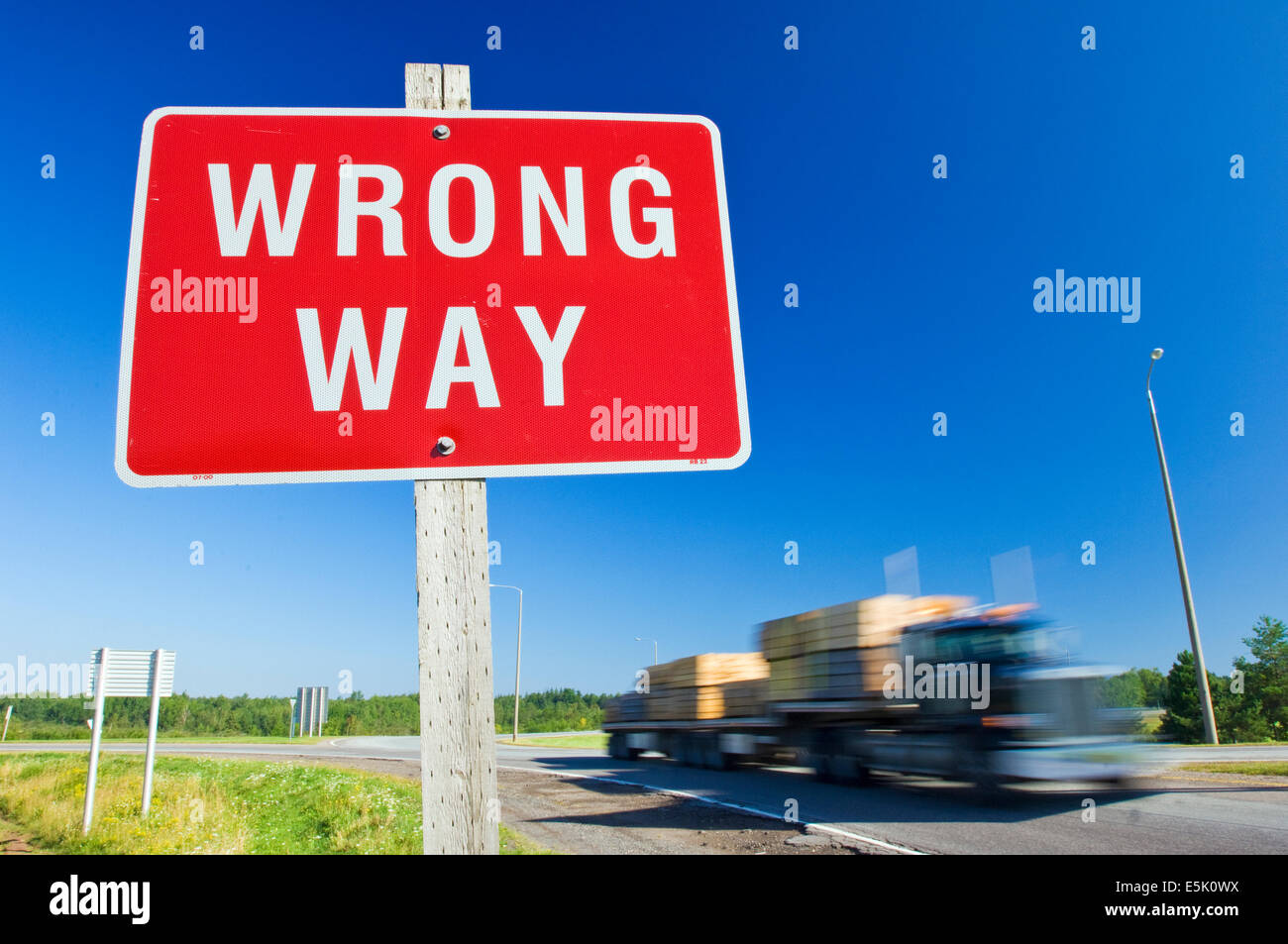 A red Wrong Way road sign against a clear blue sky with a truck approaching on the road - Stock Image
