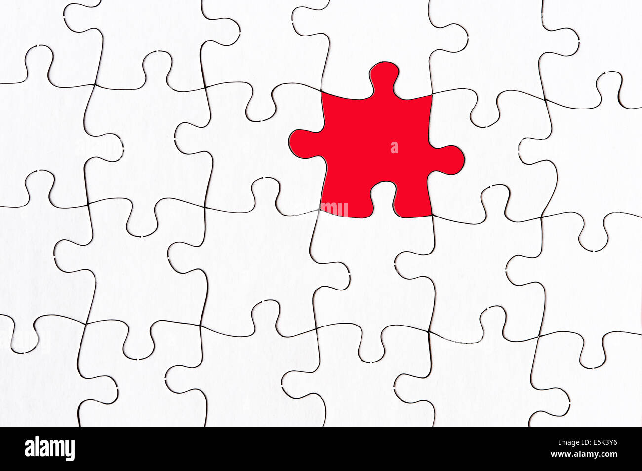 blank white jigsaw with one red piece stand out from the crowd concept - Stock Image