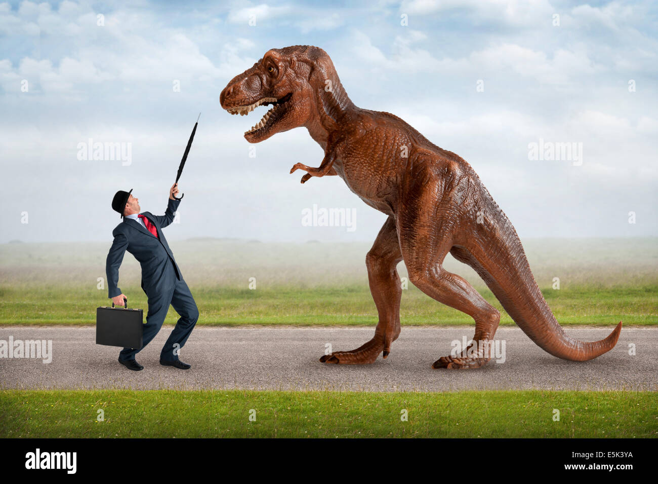 hostile business takeover concept businessman and tyrannosaurus dinosaur - Stock Image