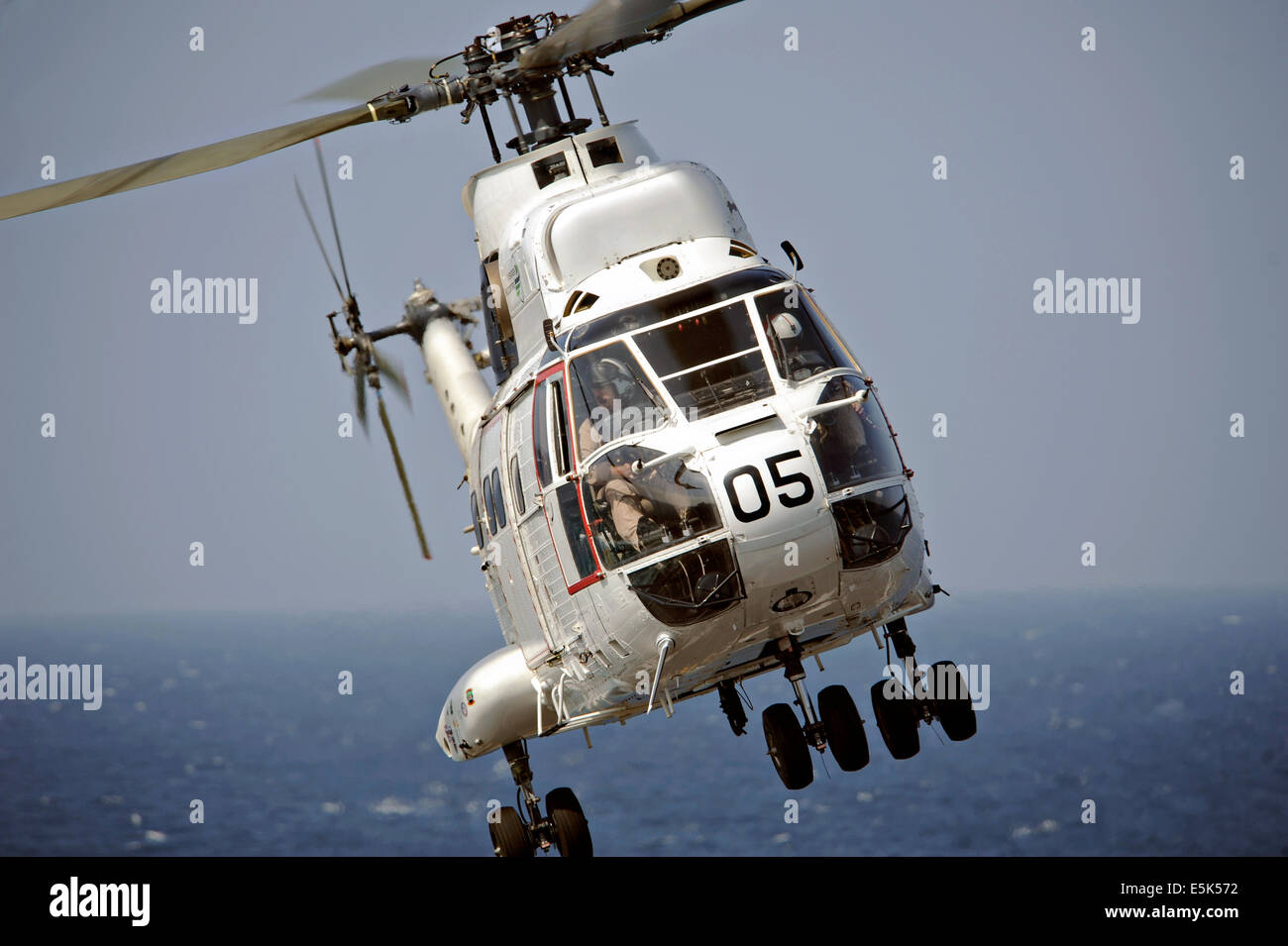 A US Navy SA-330J Puma helicopter ferries cargo from the Military Sealift Command dry cargo and ammunition ship - Stock Image