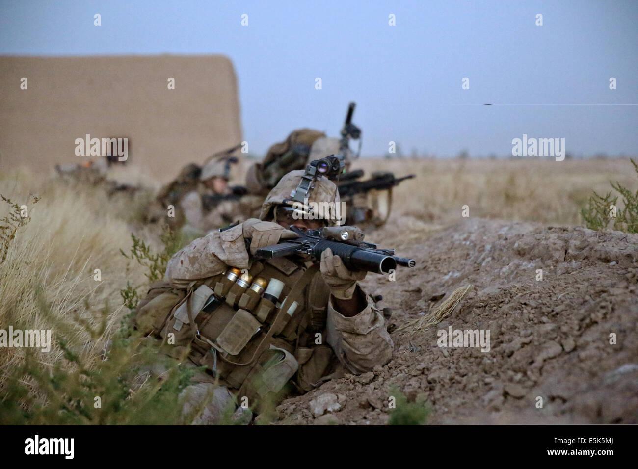 US Marine Cpl Deshaun Jackson, rifleman, Bravo Company, 1st Battalion, 7th Marine Regiment, takes cover behind a Stock Photo