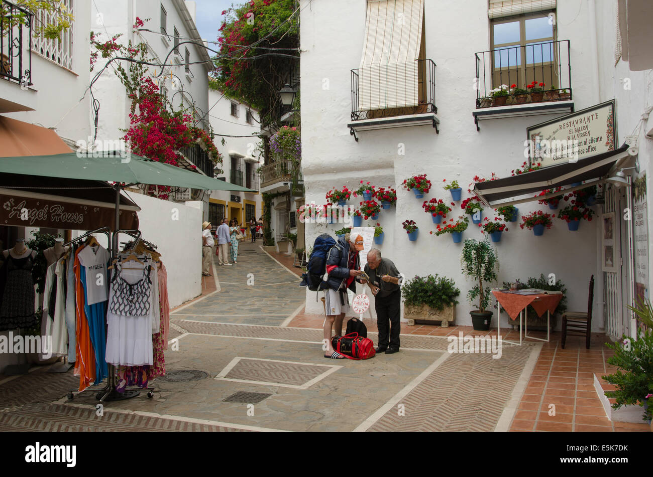 Young tourist asking a local old man for directions in old Town (Casco Antiguo), Marbella, Spain. - Stock Image