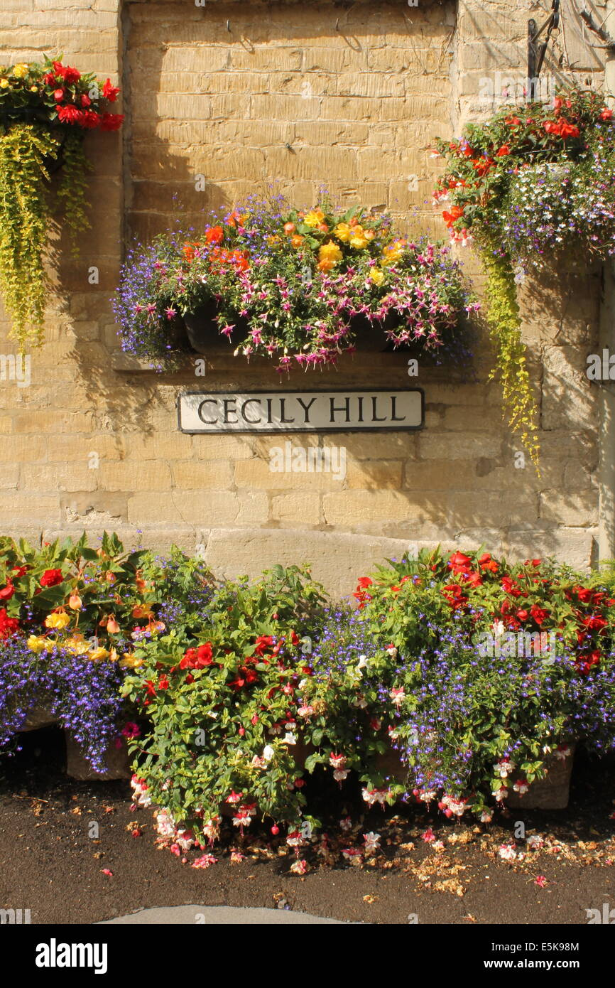 Colourful hanging baskets and warm honey-coloured Cotswold stone, Cecily Hill, Cirencester, Gloucestershire, England, - Stock Image