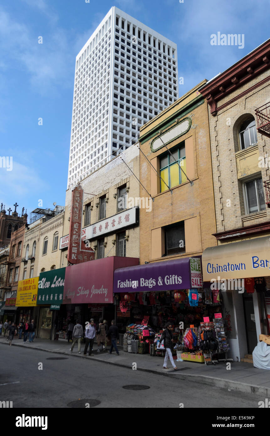 Shops and people in Grant Avenue, Chinatown, San Francisco, with a sky scraper in the background - Stock Image