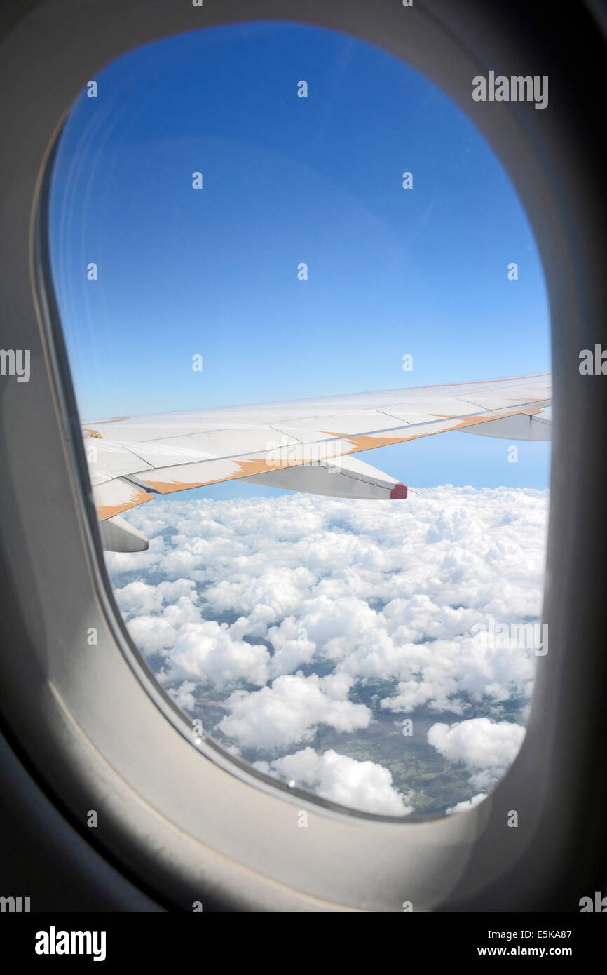 Passengers View Of Aeroplane Window Frame And Aircraft Wing With White  Clouds And A Blue Sky Flying Over Europe