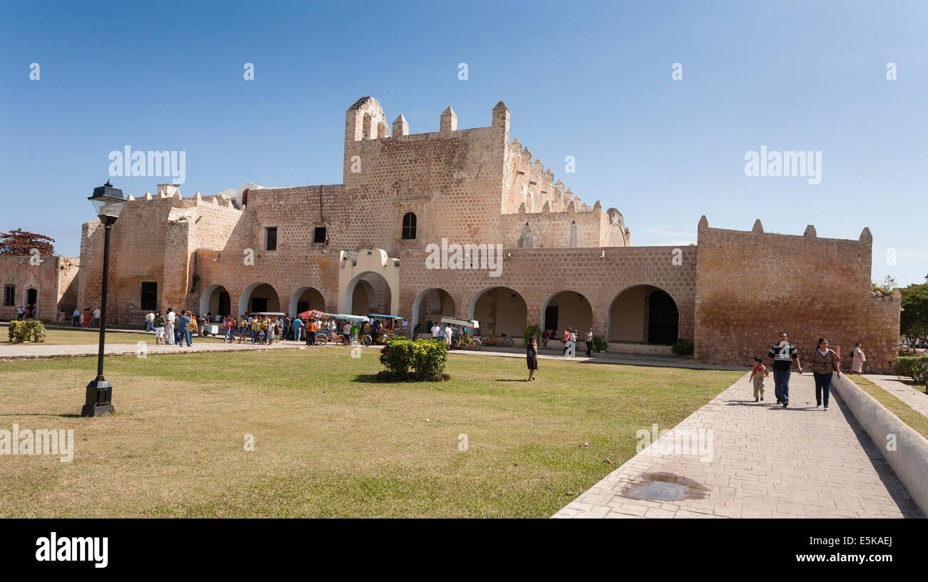 A family of 3 leaves Convento Service. A crowd gathers around the vendors waiting at the exit to the church service - Stock Image