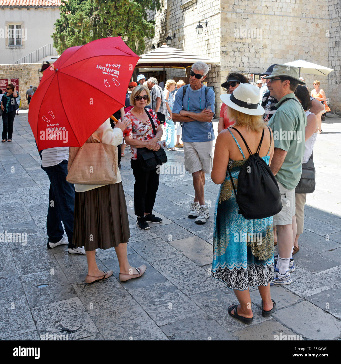 Dubrovnik Croatia walking tour guide with small group of tourists standing in the shade on a very hot summer day - Stock Image
