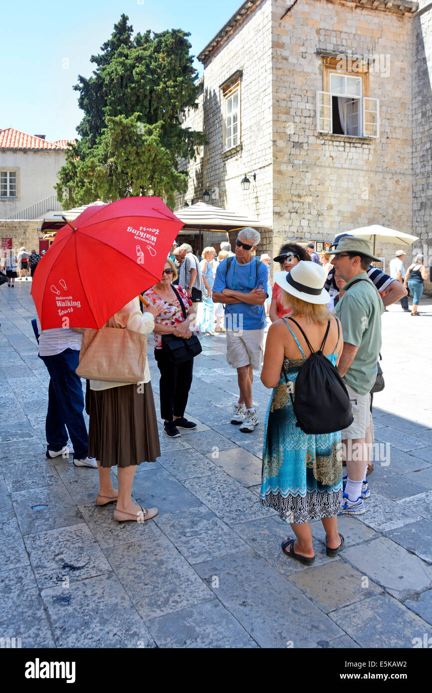 Dubrovnik walking tour guide with small group of tourists standing in the shade on a hot summer day - Stock Image
