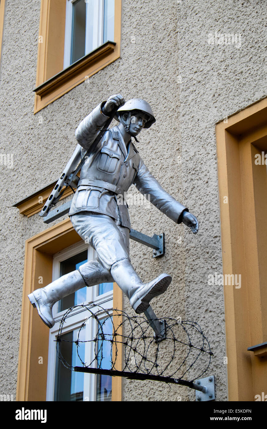 Statue of East German border guard escaping to freedom across Berlin Wall at Bernauer Strasse in Berlin Germany - Stock Image