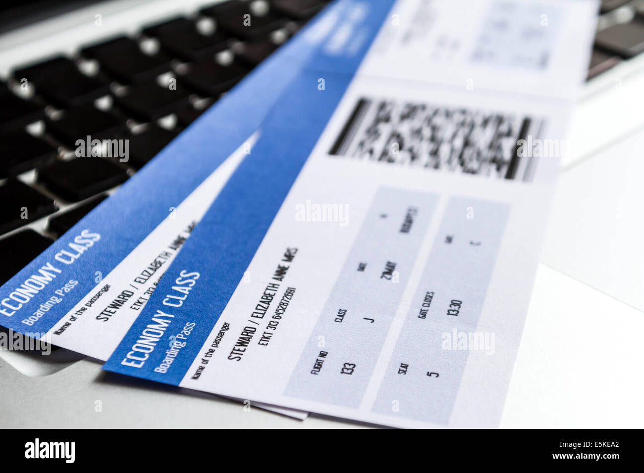 Airline tickets over the keyboard of a laptop - Stock Image