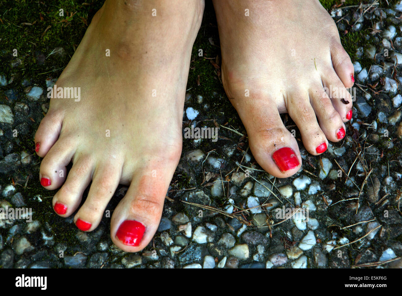 bare feet with red-colored nails - Stock Image