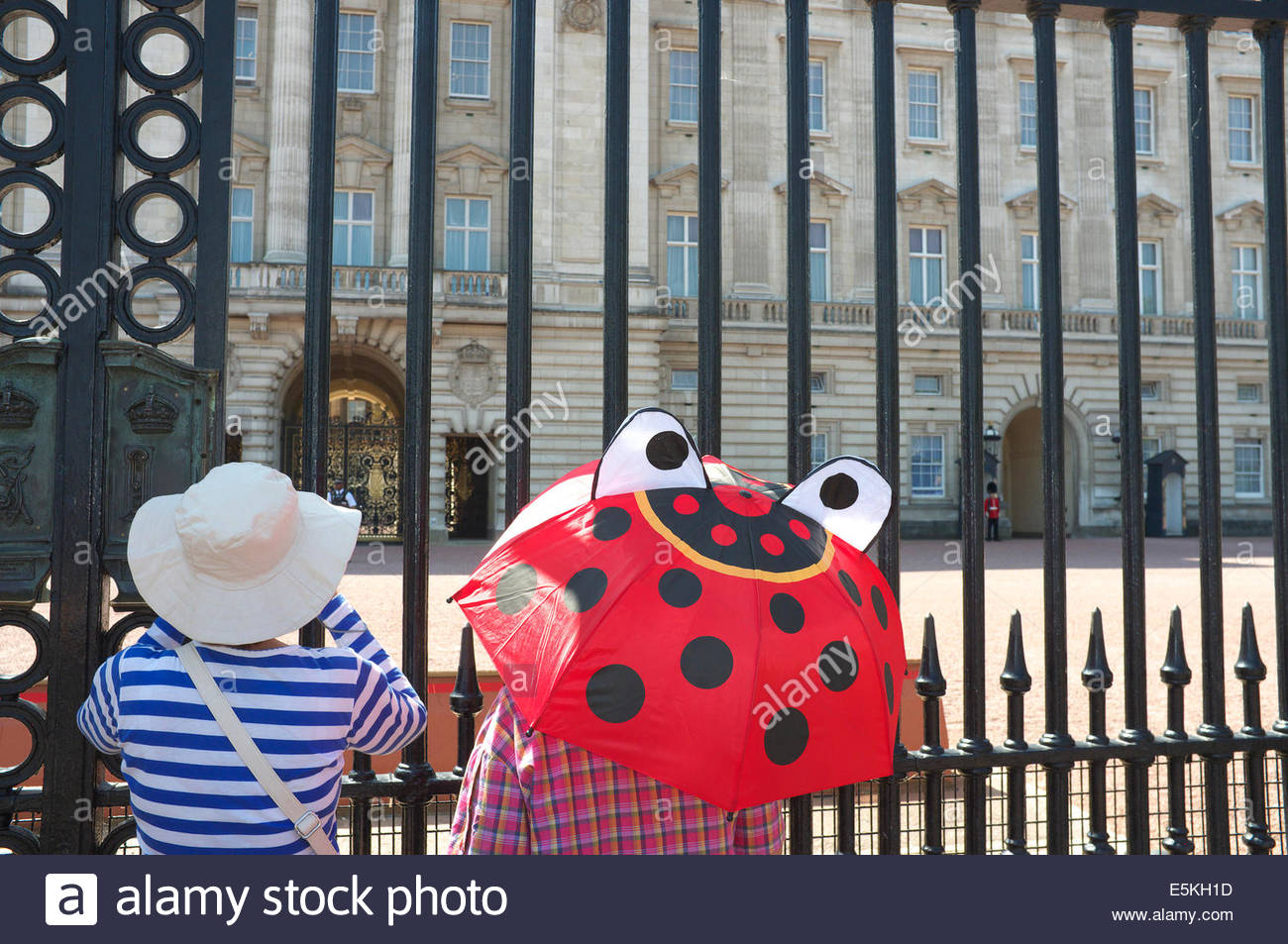 A couple of tourists, dressed in summer clothing, look through the gates of Buckingham Palace, in London, UK. - Stock Image