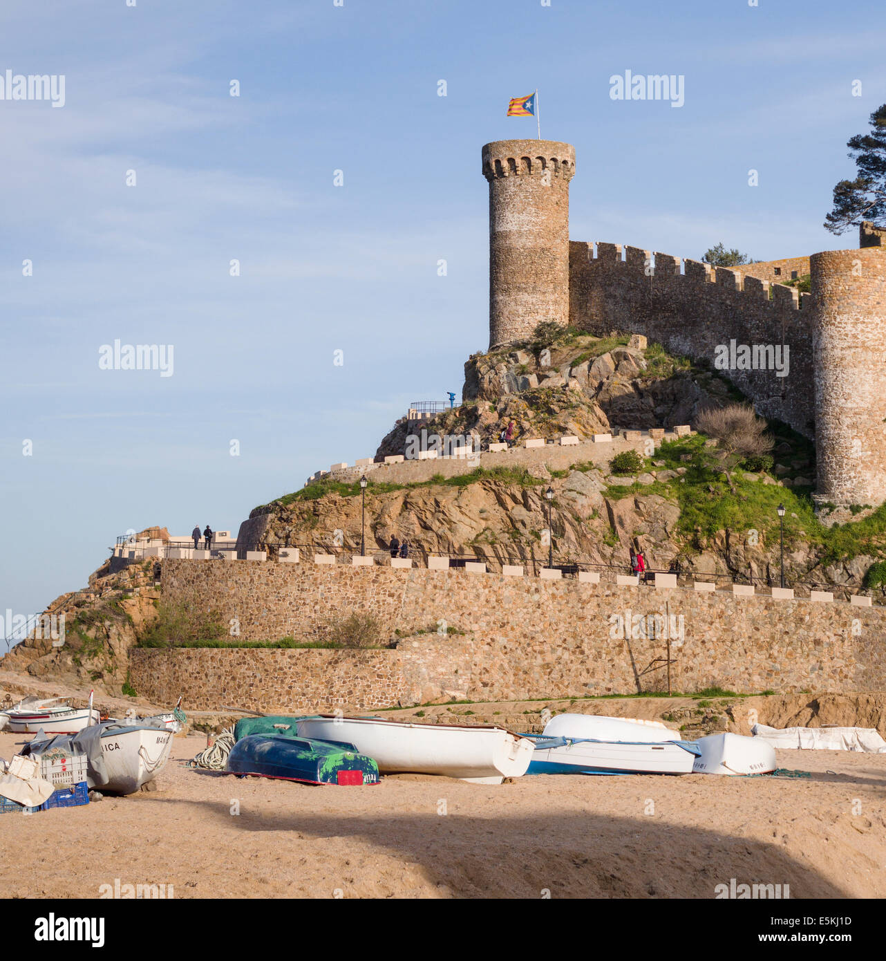 Fortress of Tossa de Mar topped by a Catalonian Flag, boats belo. The massive stone defensive wall and tower of - Stock Image