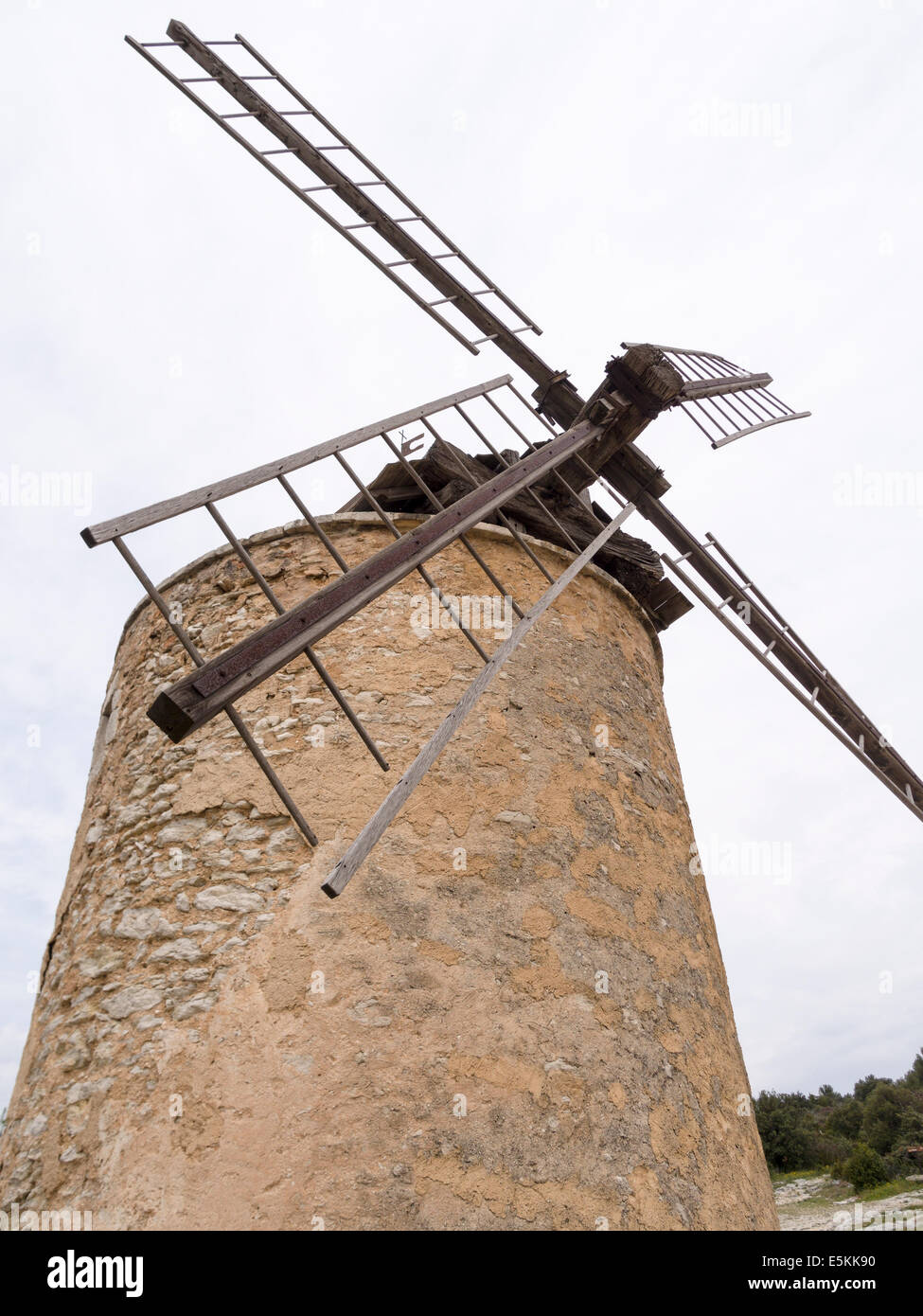 Old disused Windmill high above the village. The stone tower topped by wooden vanes warped and split by the weather. - Stock Image