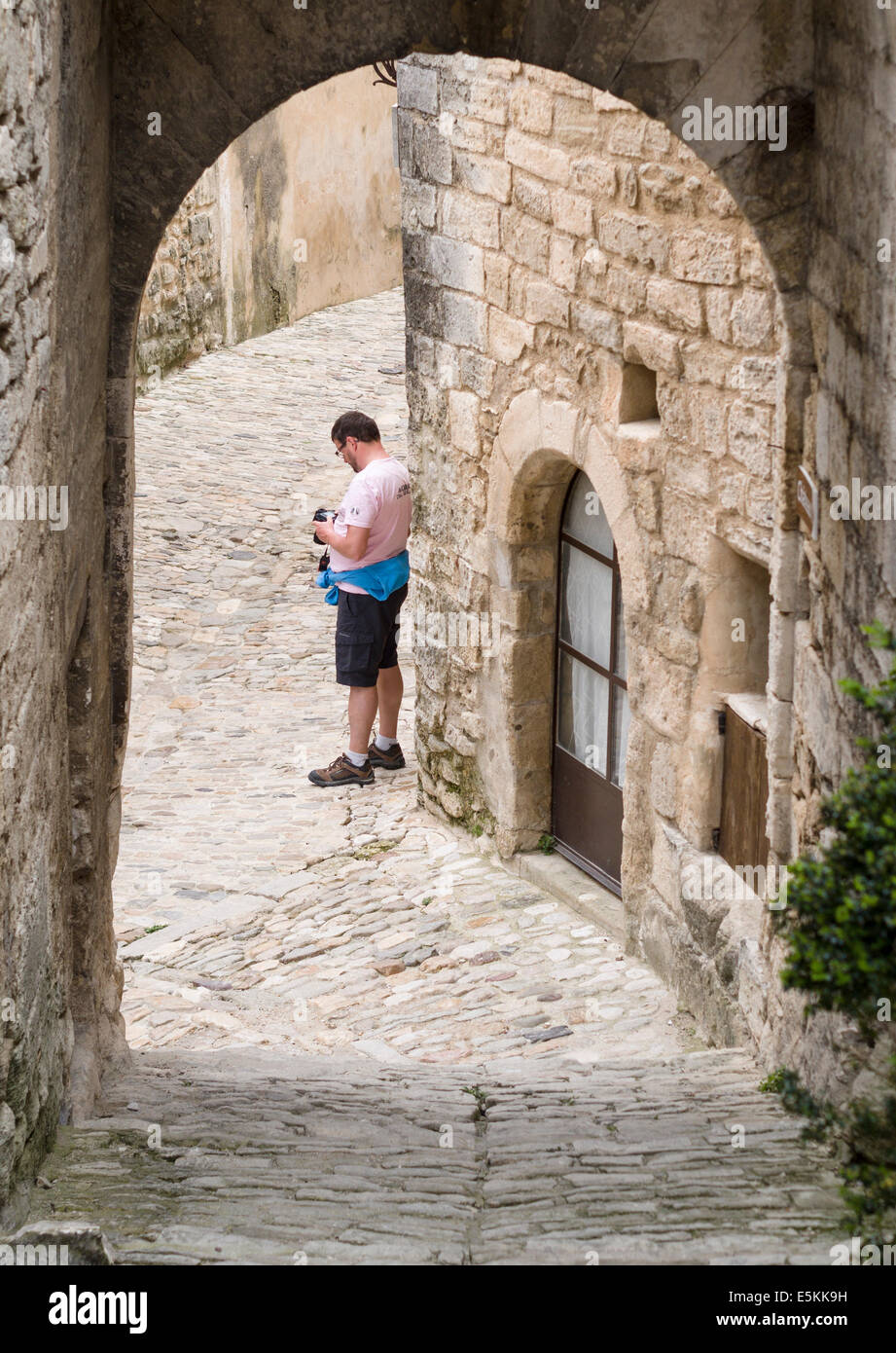 Chimping a Photograph. A tourist stands in the old Medieval village of Lacoste and checks the exposure on his SLR - Stock Image