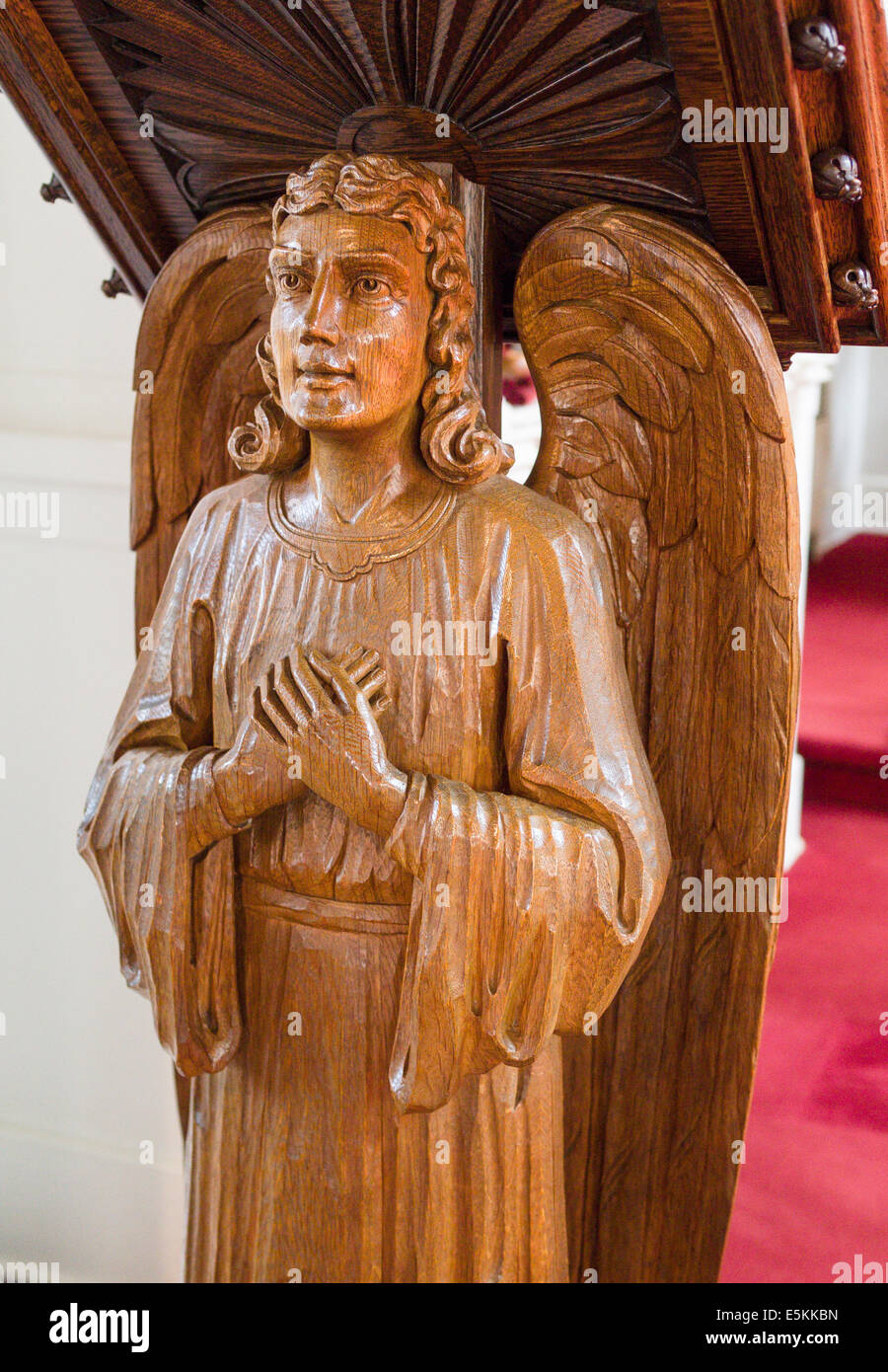 Angel Carved from a single Piece of Oak Wood. A carved winged man decorates the lectern at St Paul Lutheran Church. - Stock Image