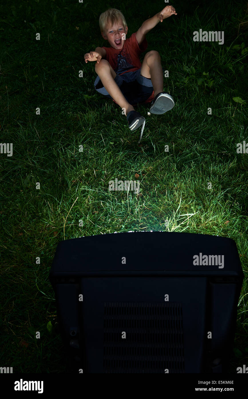 Child Blond Boy Watching Television in Yard, outside in green grass lawn, emotional, facial expression, grimace, - Stock Image