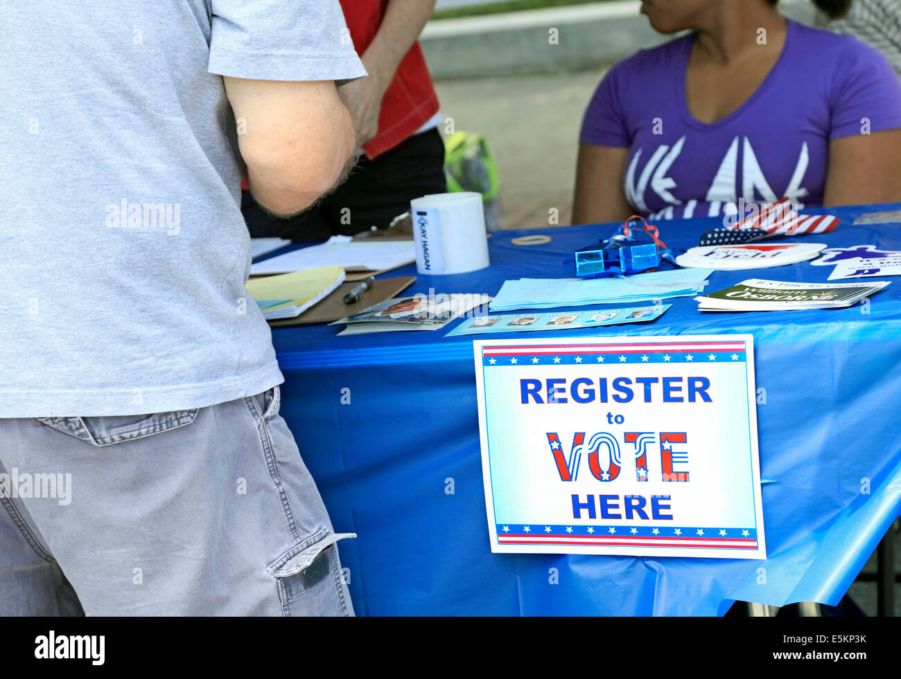 Young man at Democratic party Voting registration booth with sign. - Stock Image