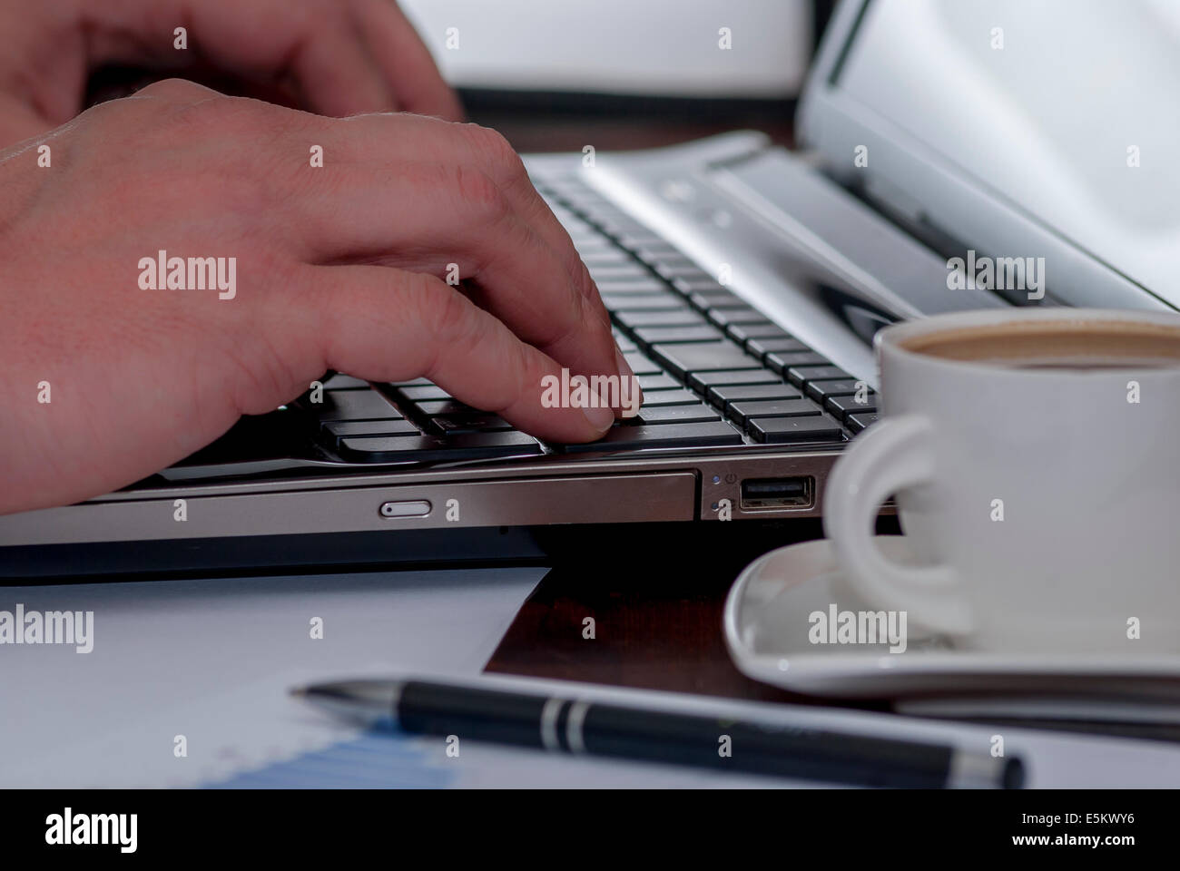 Man works in bussiness office with computer or laptop or notebook and papper graf and he drinks coffee - Stock Image