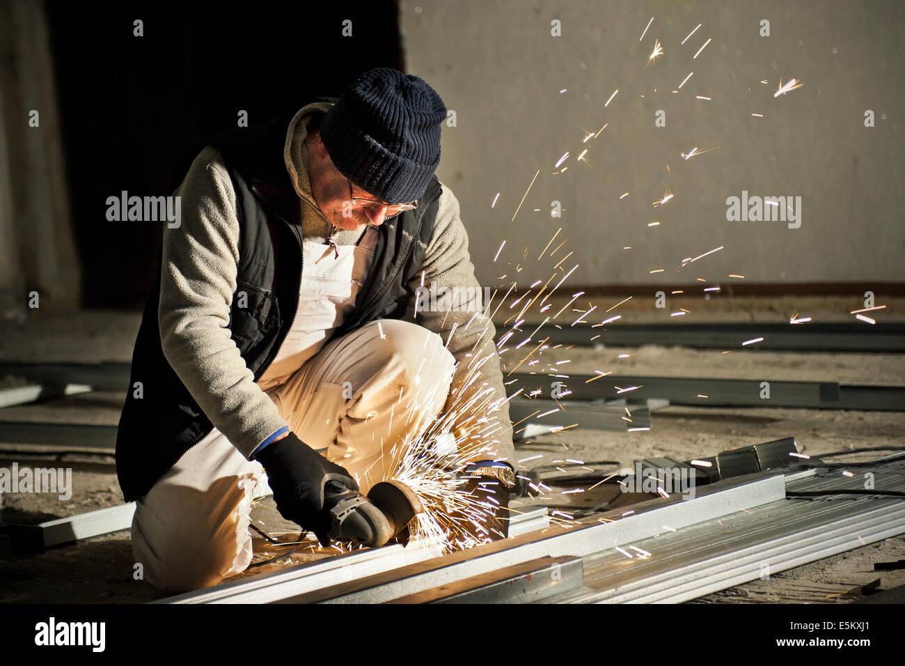 Man at work cutting metal - Stock Image