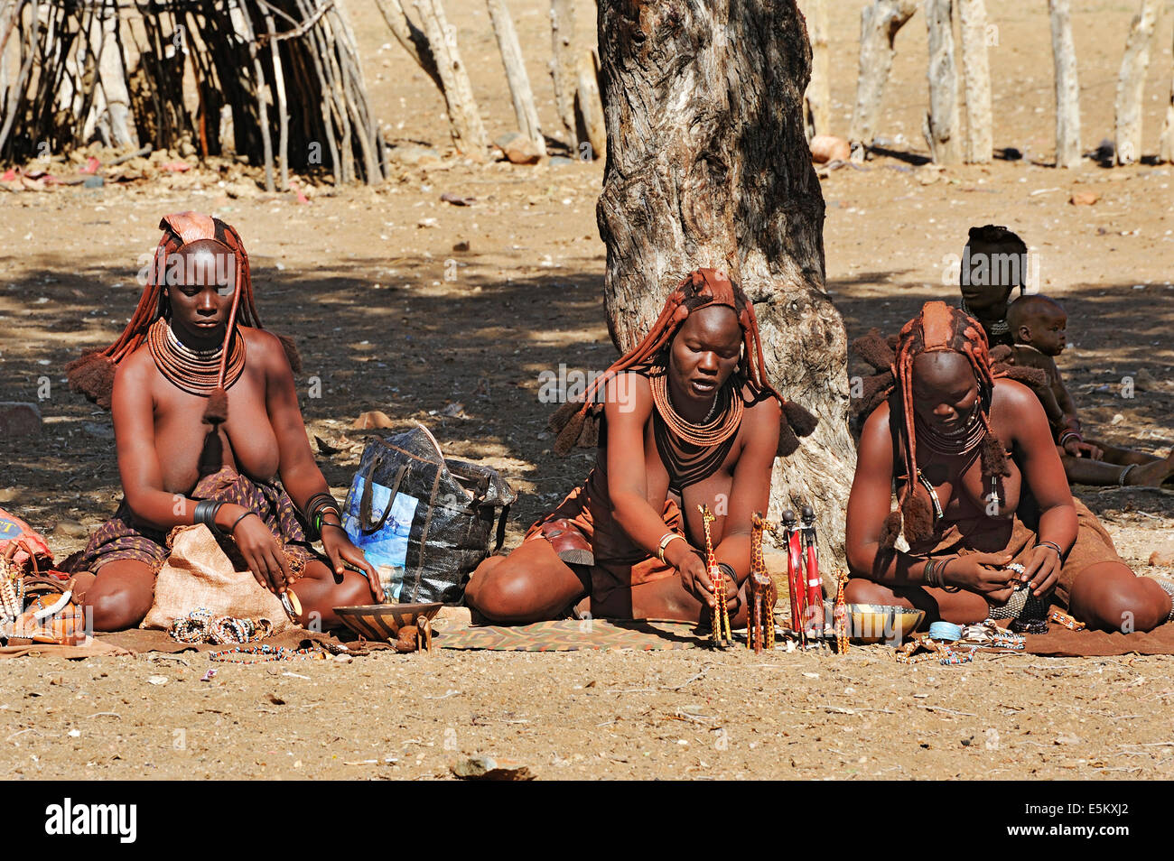 Women selling carvings in a Himba village, near Opuwo, Namibia - Stock Image