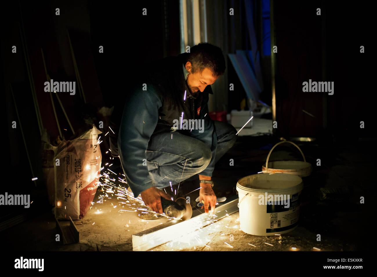 Man at work cutting metal profiles - Stock Image