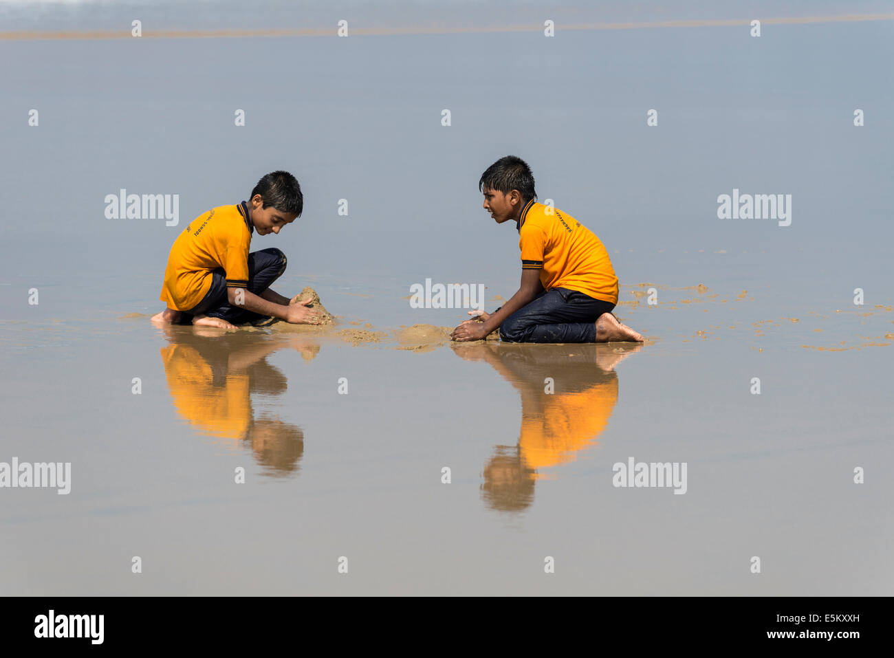 Two schoolboys wearing yellow shirts playing on the beach, reflection, Varkala, Kerala, India Stock Photo