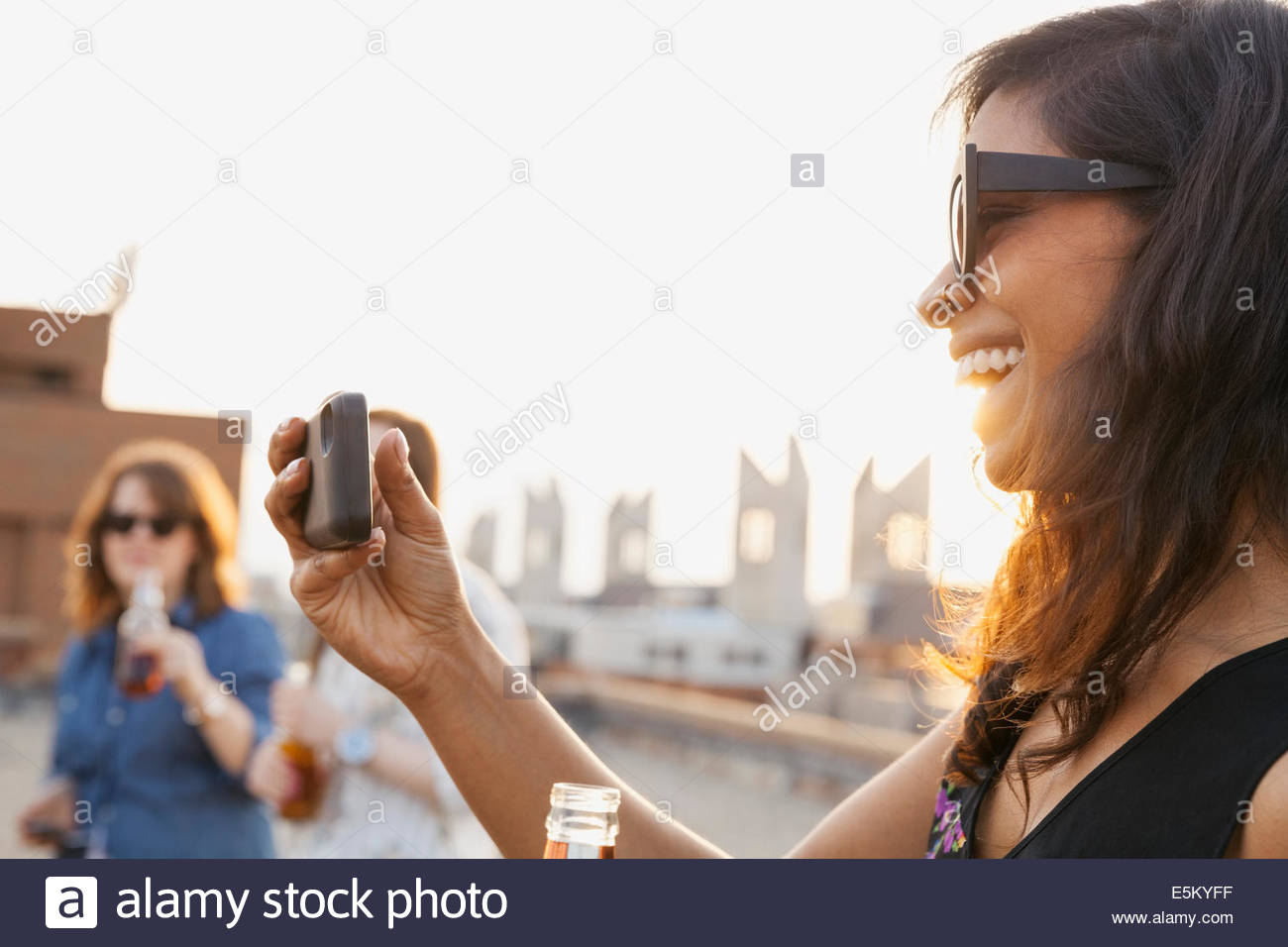 Smiling woman taking photos at urban rooftop party - Stock Image