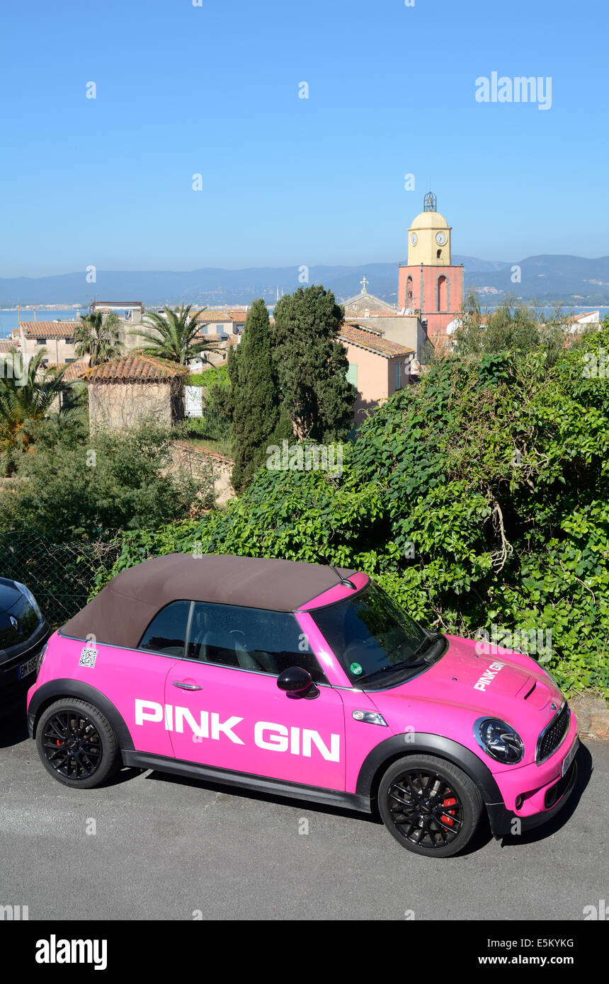 Pink Gin Advertising Car, Publicity Car or Pink Mini Cooper Convertible in front of View of Saint Tropez Old Town - Stock Image