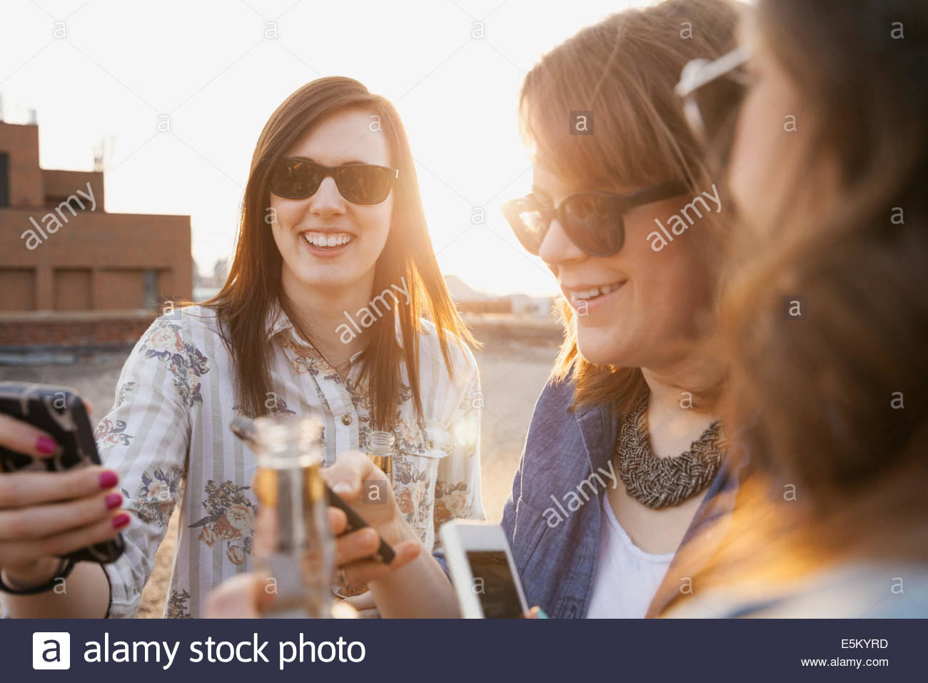 Friends drinking beer and text messaging on rooftop - Stock Image
