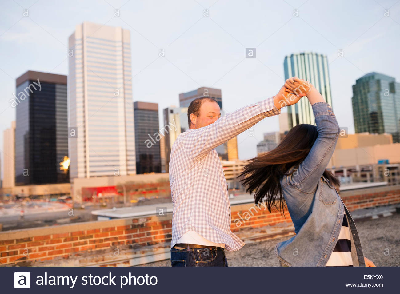 Couple dancing on urban rooftop - Stock Image