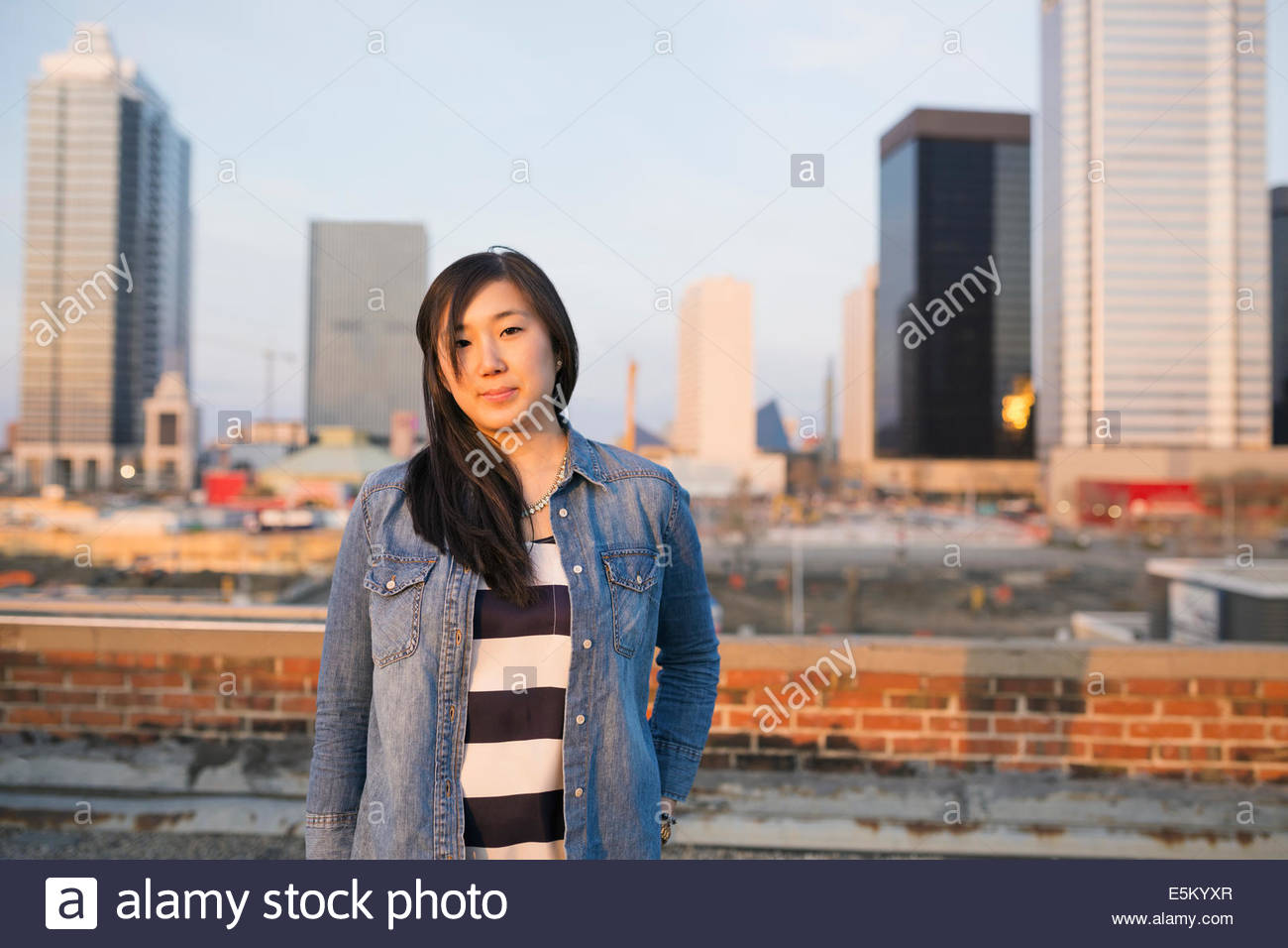 Portrait of woman on urban rooftop - Stock Image