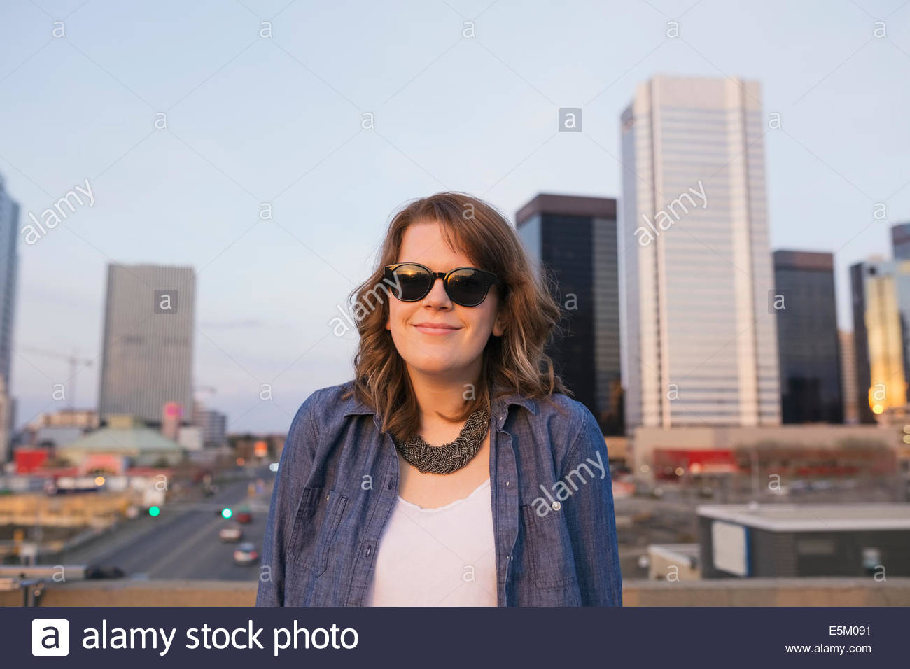 Portrait of smiling woman on urban rooftop - Stock Image
