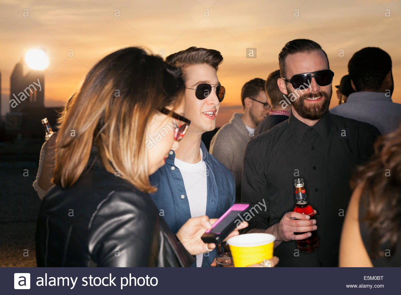 Friends drinking and talking at rooftop party - Stock Image