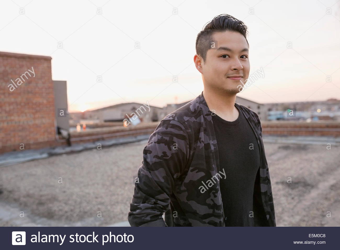 Portrait of smiling man on rooftop - Stock Image
