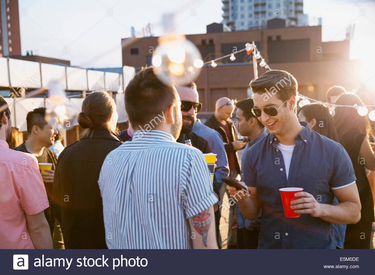 Crowd enjoying urban rooftop party - Stock Image